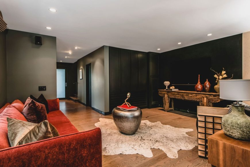 A sideway view at this living room featuring a red sofa set with a flat-screen TV in front. There's a fireplace in the corner with a stylish sitting chair on the side. Images courtesy of Toptenrealestatedeals.com.