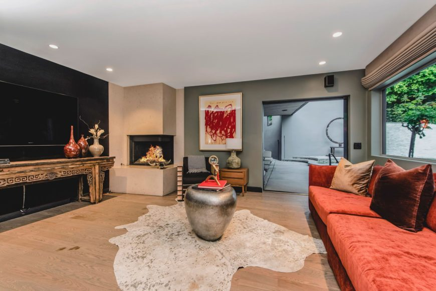 This living space features a red sofa set and a fireplace in the corner with a sitting chair on the side. Images courtesy of Toptenrealestatedeals.com.