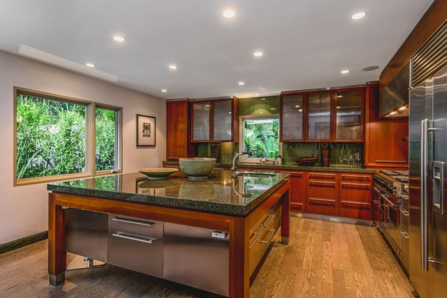 This view showcases the kitchen's L-shaped style with a large center island lighted by recessed ceiling lights. Images courtesy of Toptenrealestatedeals.com.