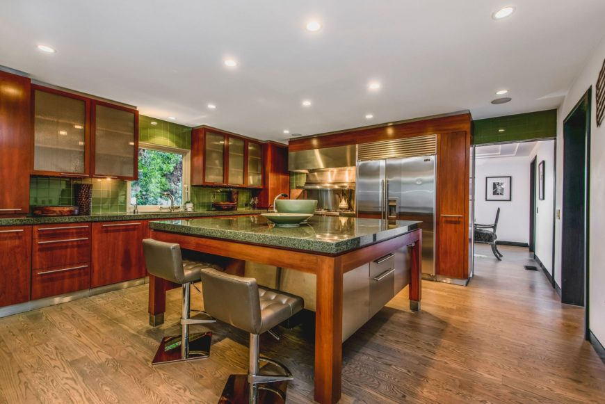 A complete look of the kitchen focusing on its large center island with a granite countertop and has space for a breakfast bar for two. Images courtesy of Toptenrealestatedeals.com.