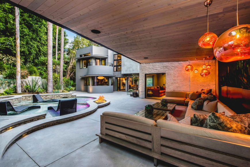 Another view of the modern outdoor living space set lighted by charming lighting. There's the custom swimming pool on the side. Images courtesy of Toptenrealestatedeals.com.