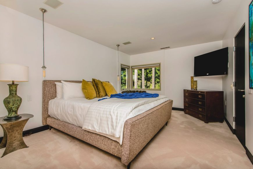 A guest room with a massive bed setup and has a large flat-screen TV set in the corner of the wall. The room has carpeted flooring as well. Images courtesy of Toptenrealestatedeals.com.