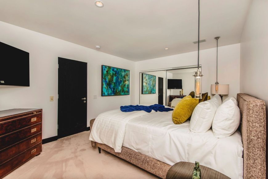 A guest room featuring a classy bed set lighted by a table lamp on the side and pendant lights hanging from the ceiling. There's a flat-screen TV on the wall as well. Images courtesy of Toptenrealestatedeals.com.