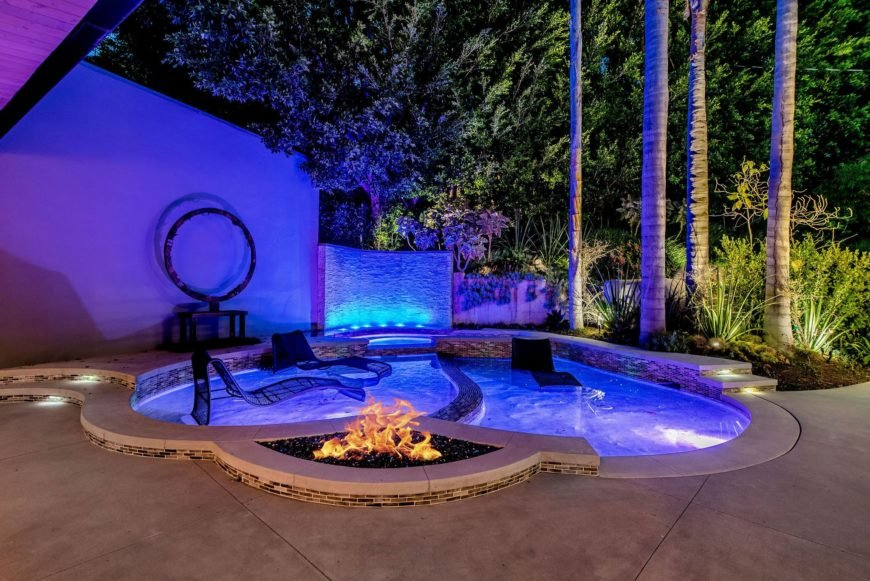 A focused look at the custom swimming pool with all the lighting on. The combined blue and purple colors are just amazing. Images courtesy of Toptenrealestatedeals.com.