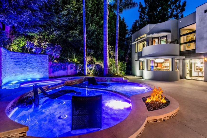 A focused look at the outdoor custom swimming pool with a fire pit during night time when the night lights are on. Absolute stunner. Images courtesy of Toptenrealestatedeals.com.