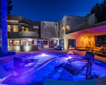 Another look at both the outdoor custom swimming pool and the outdoor living space, this time facing the house while the lighting are on. Images courtesy of Toptenrealestatedeals.com.