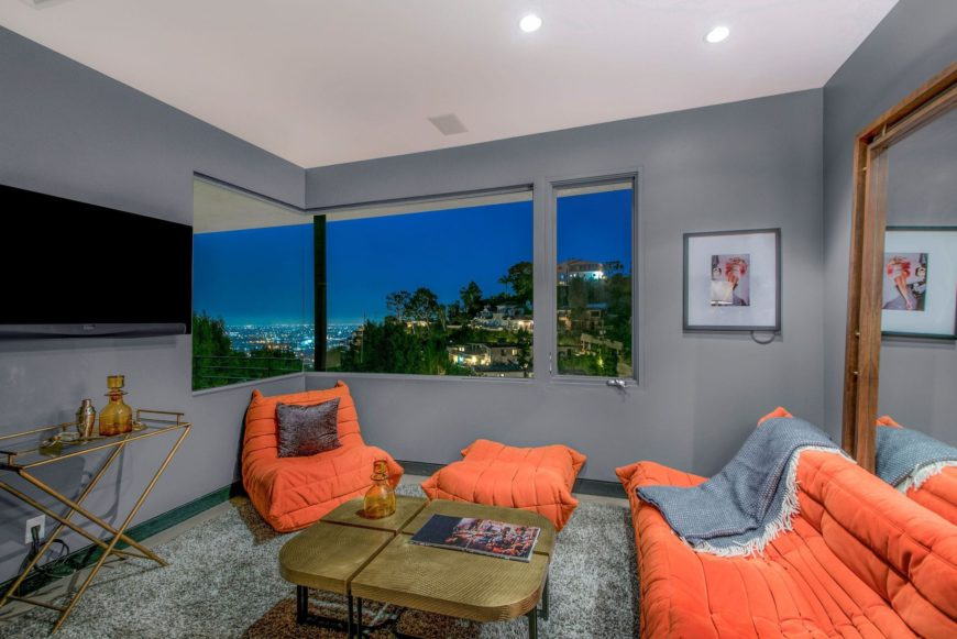 A small living room featuring stylish orange seats and a gorgeous center table, along with a flat-screen TV on the wall, set near the glass windows. Images courtesy of Toptenrealestatedeals.com.