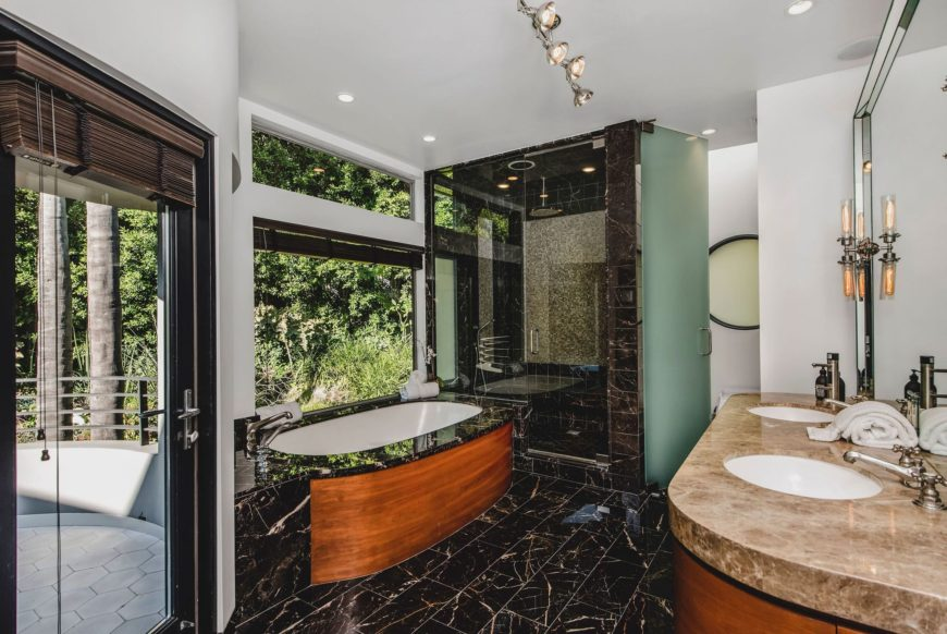 Another look at the primary bathroom, this time focusing on the double sink with a marble counter, a drop-in soaking tub near the window and a walk-in shower room. Images courtesy of Toptenrealestatedeals.com.