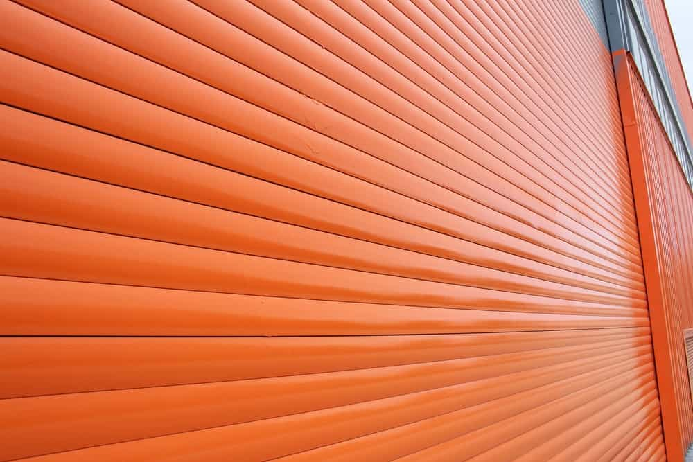 A close-up view of this newly painted bright orange aluminum siding of this Industrial-style home.