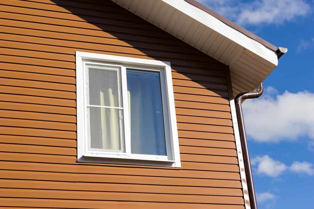 The beautiful blue sky complements the matte brown vinyl siding of this home contrasted by the white window.