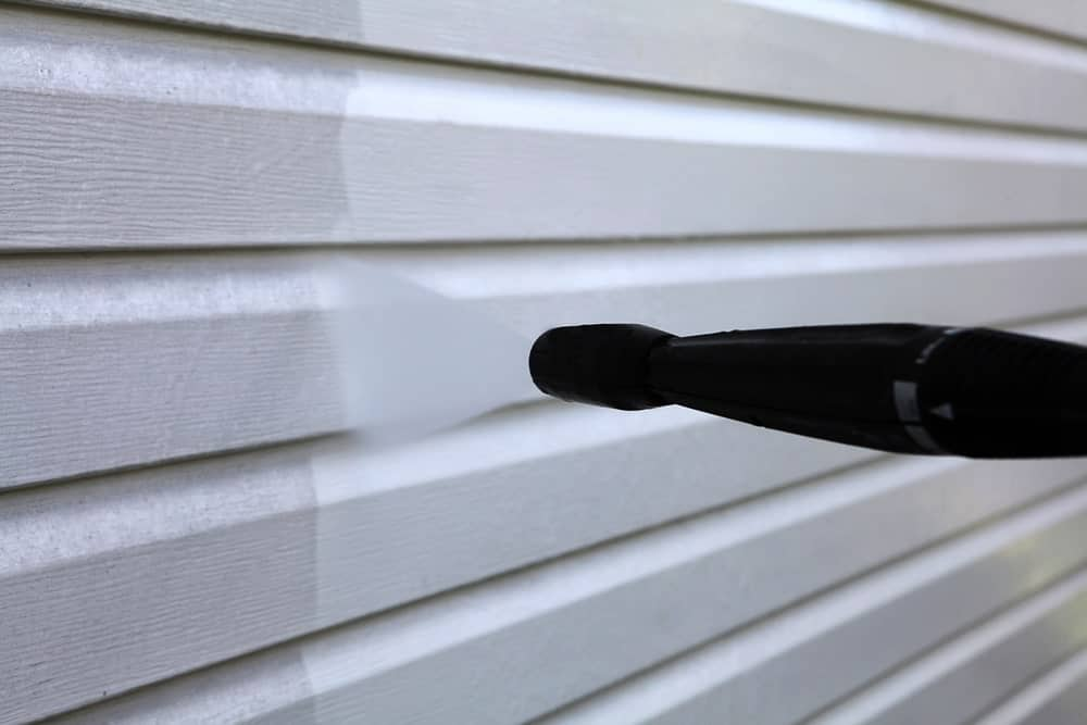 This is a close-up view of a vinyl siding on the exterior wall of a house being power washed.