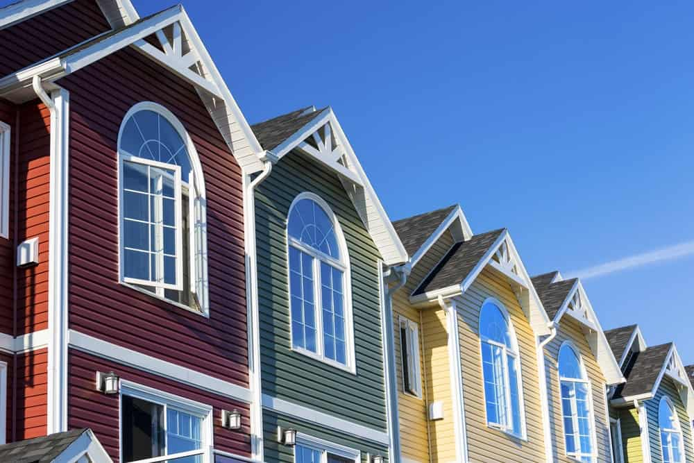 A colorful row of similar townhouses with the same vinyl sidings on their exterior walls in varying colors.