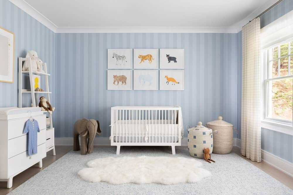 Large baby boy nursery room featuring lovely blue walls and a large area rug. There's a white nursery bed and a white drawer cabinet on the side.