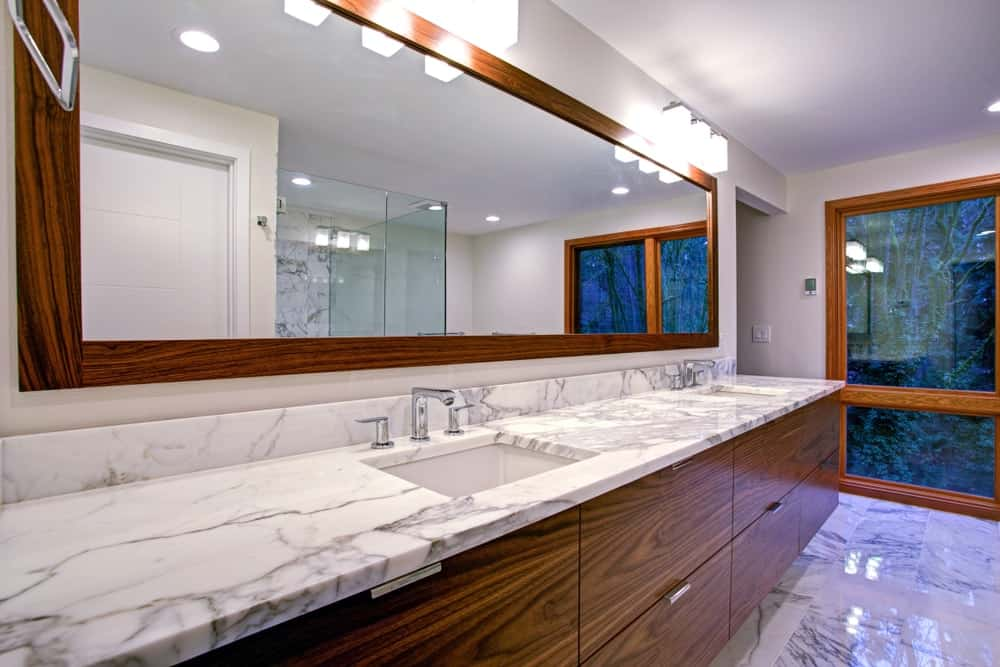 Sleek modern bathroom featuring the double sink vanity with marble countertop.