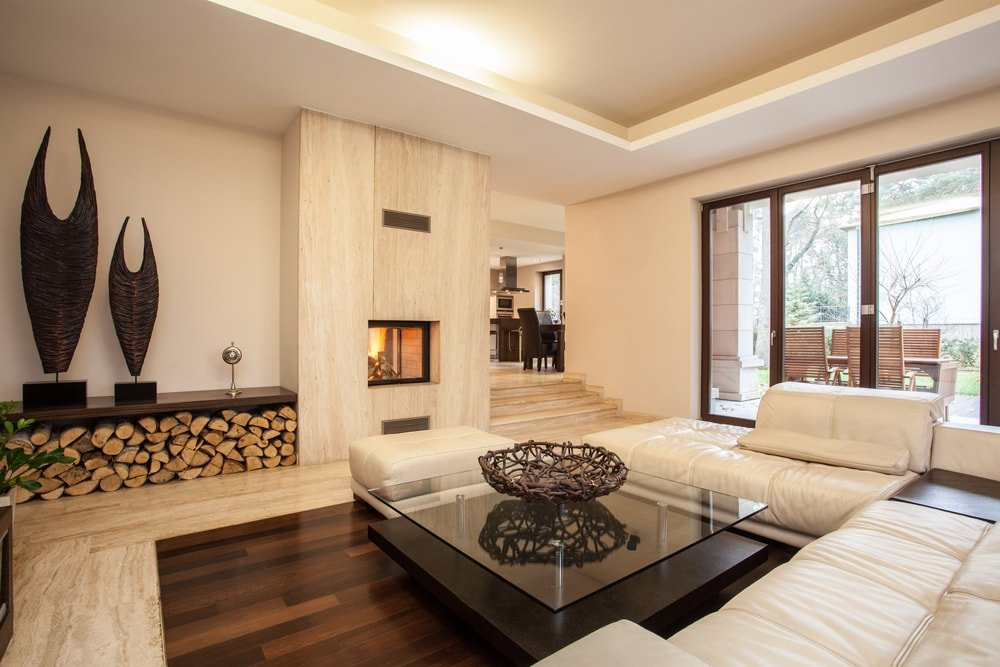 Beige living room with an embedded fireplace, glass sliding doors, and a mix of tile and wood flooring.