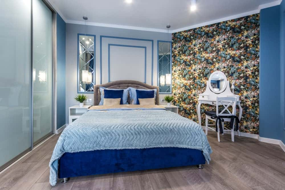 Blue primary bedroom with modern furniture, wide plank flooring, bold wallpaper, wainscoting and warm lighting.