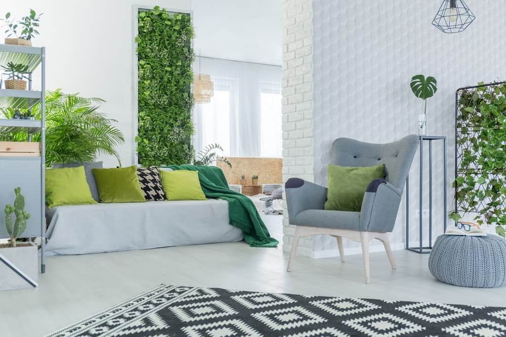 Bright living room interior with white walls and flooring, green accessories, and plenty of green indoor plants.