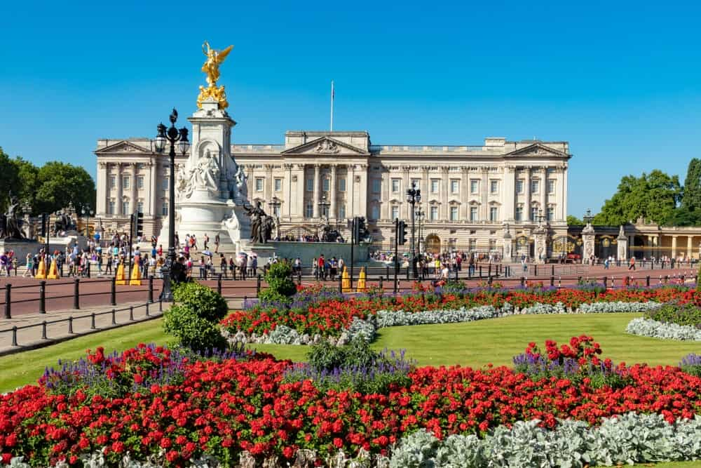 A view of her majesty, Queen Elizabeth II's residence, the Buckingham palace from its lovely garden filled with healthy plants and flowers.