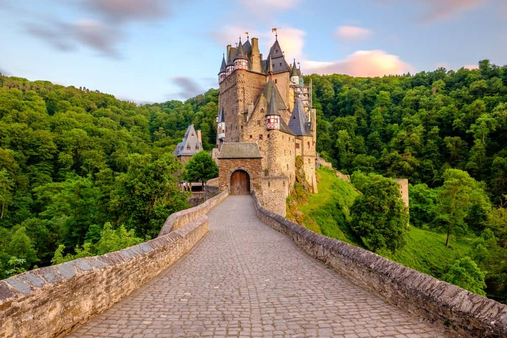 A look at the Burg Eltz in Rhineland-Palatinate, Germany. The photo was taken from the castle's walkway surrounded by countless mature and green trees.