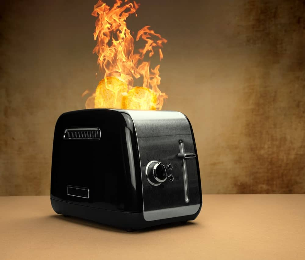 Black toaster in flames.