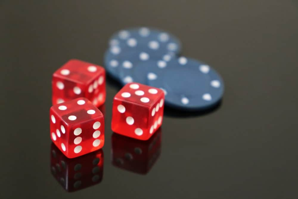 Casino red dices and gaming chips on a dark glossy surface.