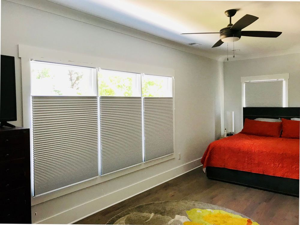 This bedroom features hardwood floors, gray walls and a regular ceiling, together with glass windows featuring window shades.