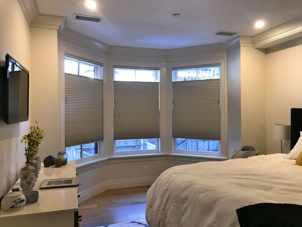 This bedroom features a large cozy bed and a widescreen TV on the wall. The windows also feature window shades. The ceiling has recessed ceiling lights.
