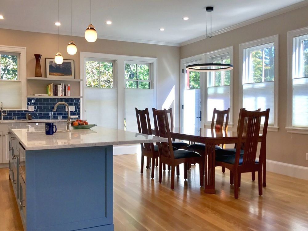 A dine-in kitchen offering a classy dining table and chairs set, along with a kitchen with a center island lighted by lined up pendant lights.
