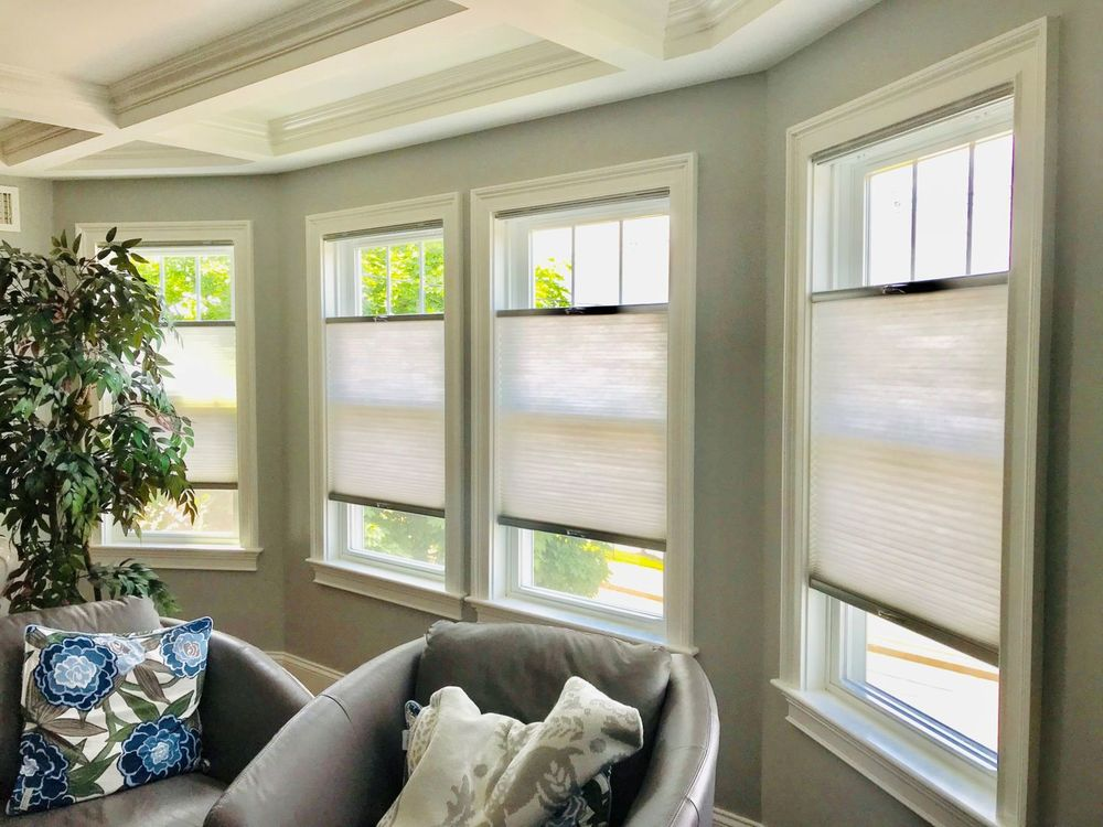 This house features gray walls and a gorgeous coffered ceiling, along with windows with window shades.