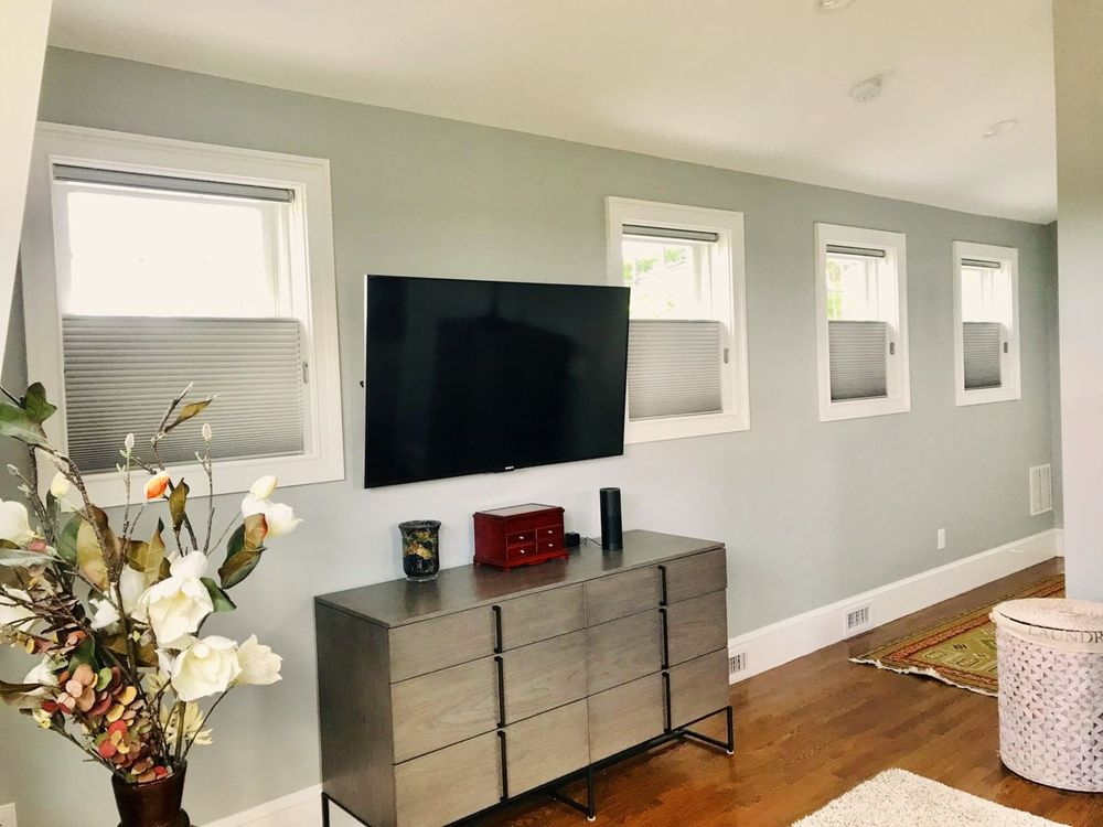 A look at this house's gray walls, windows with window shades and a large flat-screen TV set on the wall.