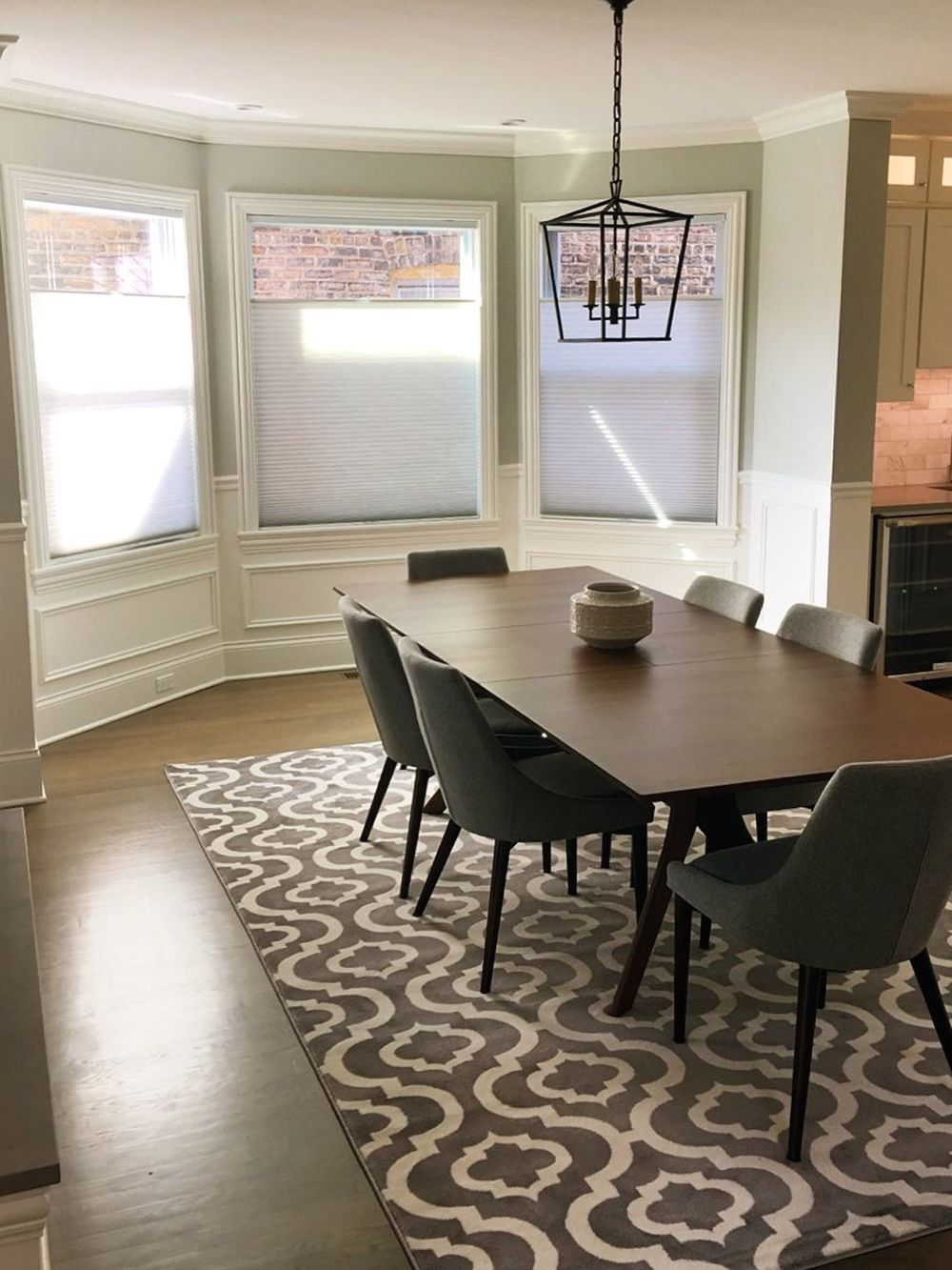 Dining area featuring a wooden dining table paired with gray modern chairs set on top of a stylish area rug covering the hardwood flooring.