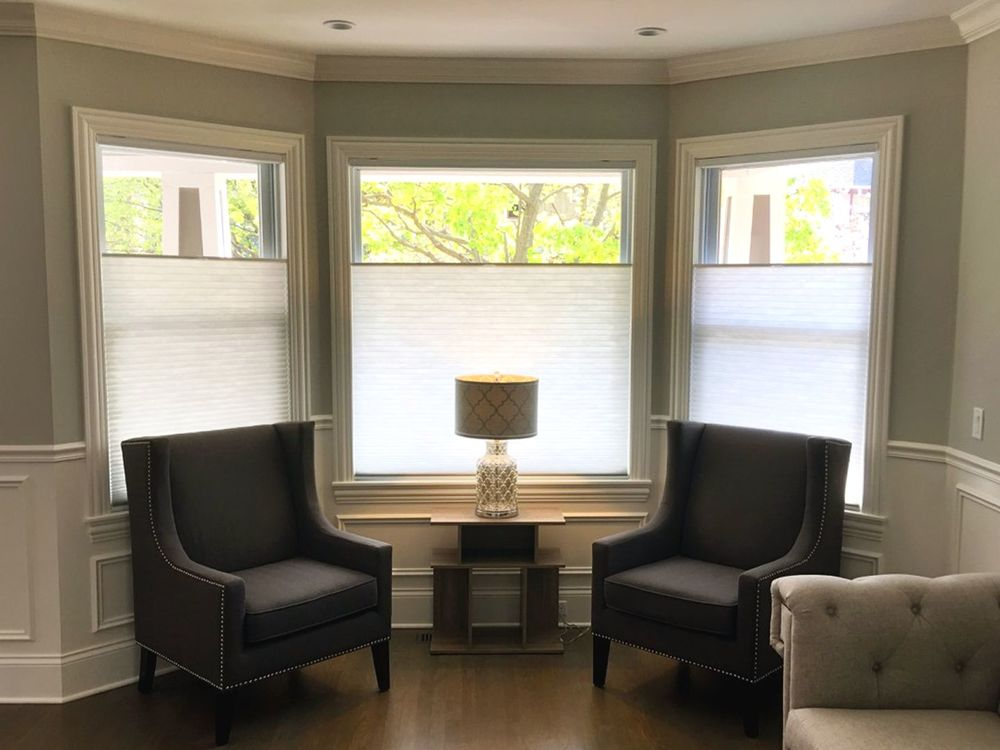 Living space featuring an elegant gray couch and a pair of black chairs with a center table topped by a table lamp set near the windows.