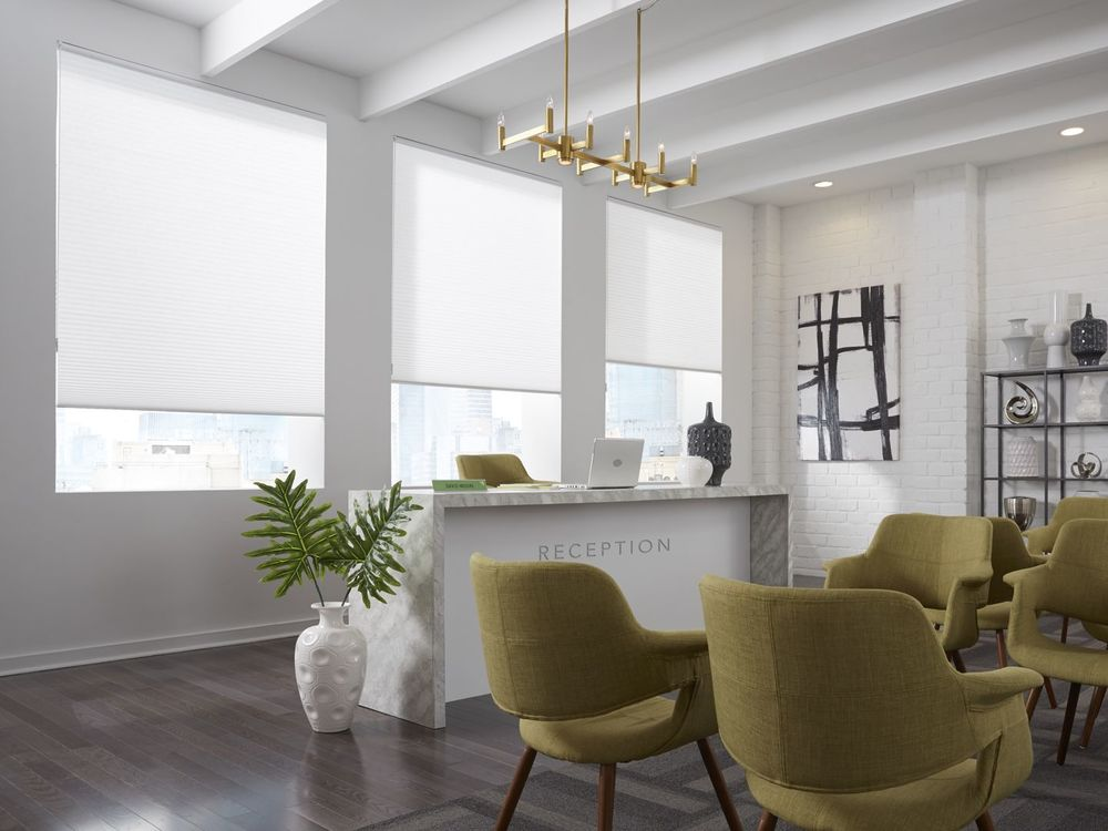 A reception room featuring multiple sitting areas and hardwood flooring, along with a tall ceiling and glass windows with window shades.