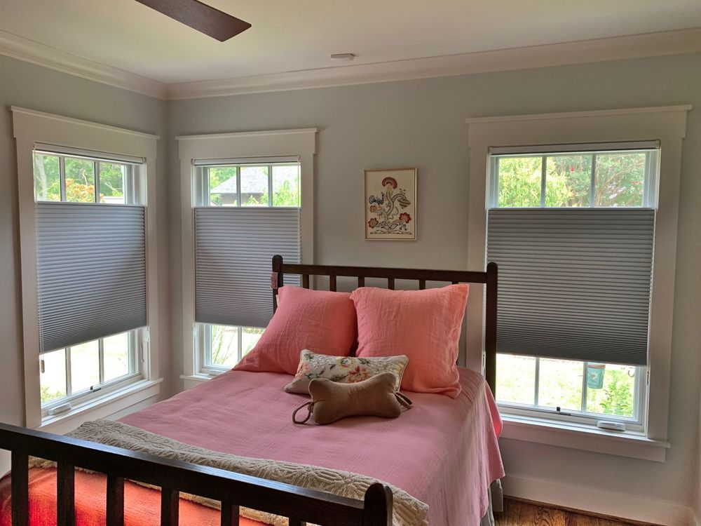 This bedroom offers a double-sized bed set near the windows with window shades. The room features light gray walls and hardwood floors.