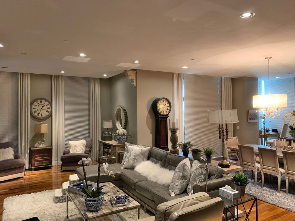This great room boasts a living space with a set of luxurious furniture and an elegant dining table set lighted by an enchanting ceiling light.