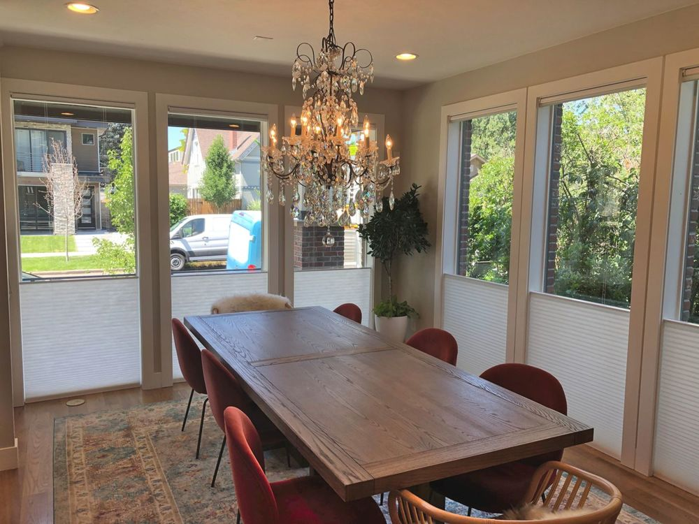 Dining room featuring gray walls, hardwood floors and a glamorous chandelier set just above the dining table set.