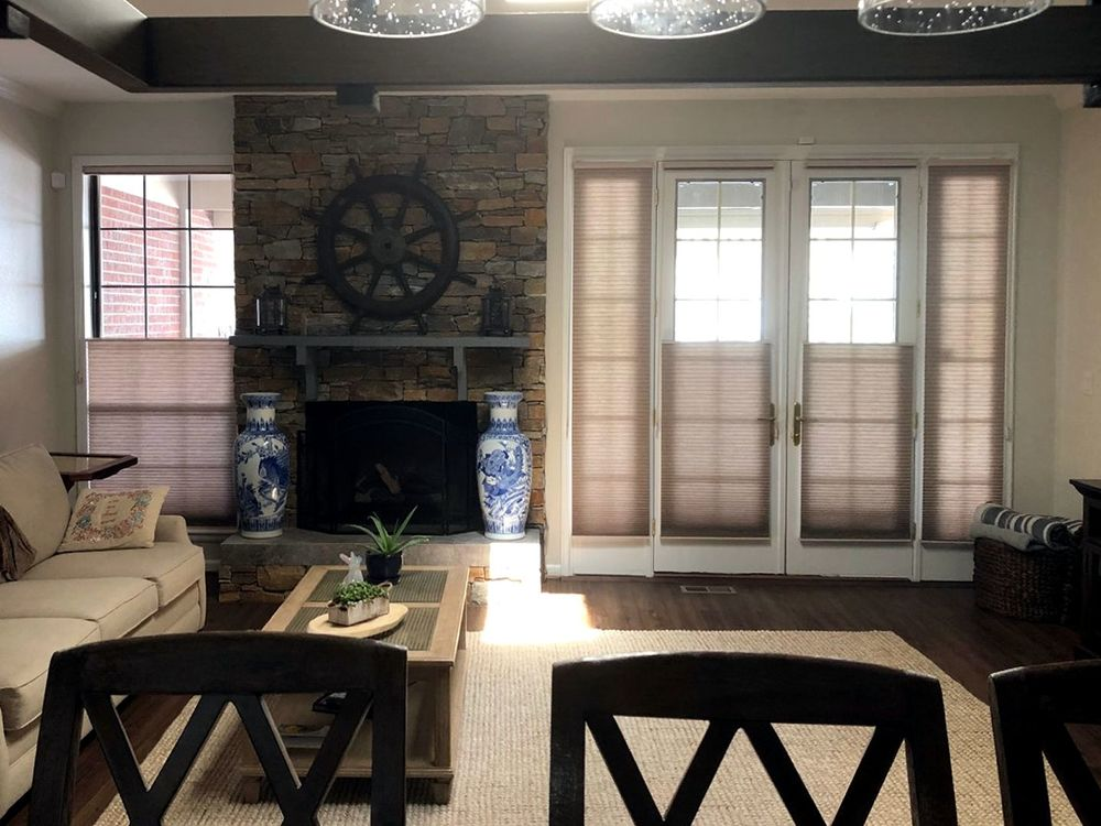 Spacious living space offering a nice comfy couch and a stylish center table on top of an area rug covering the hardwood flooring. The space also has a fireplace and bright ceiling lights.