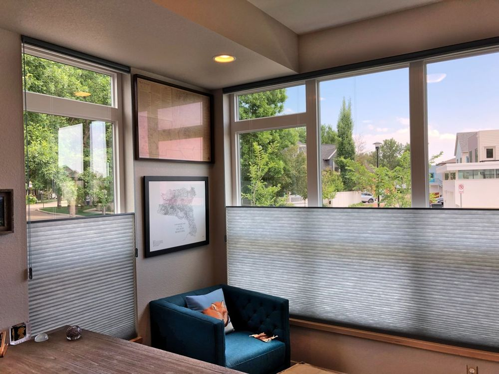 This room features gray walls and a tray ceiling, along with glass windows featuring window shades.