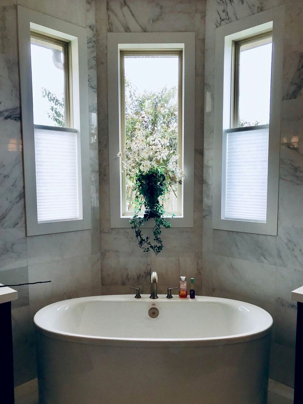 A focused look at this primary bathroom's freestanding deep soaking tub surrounded by gorgeous marble tiles walls.