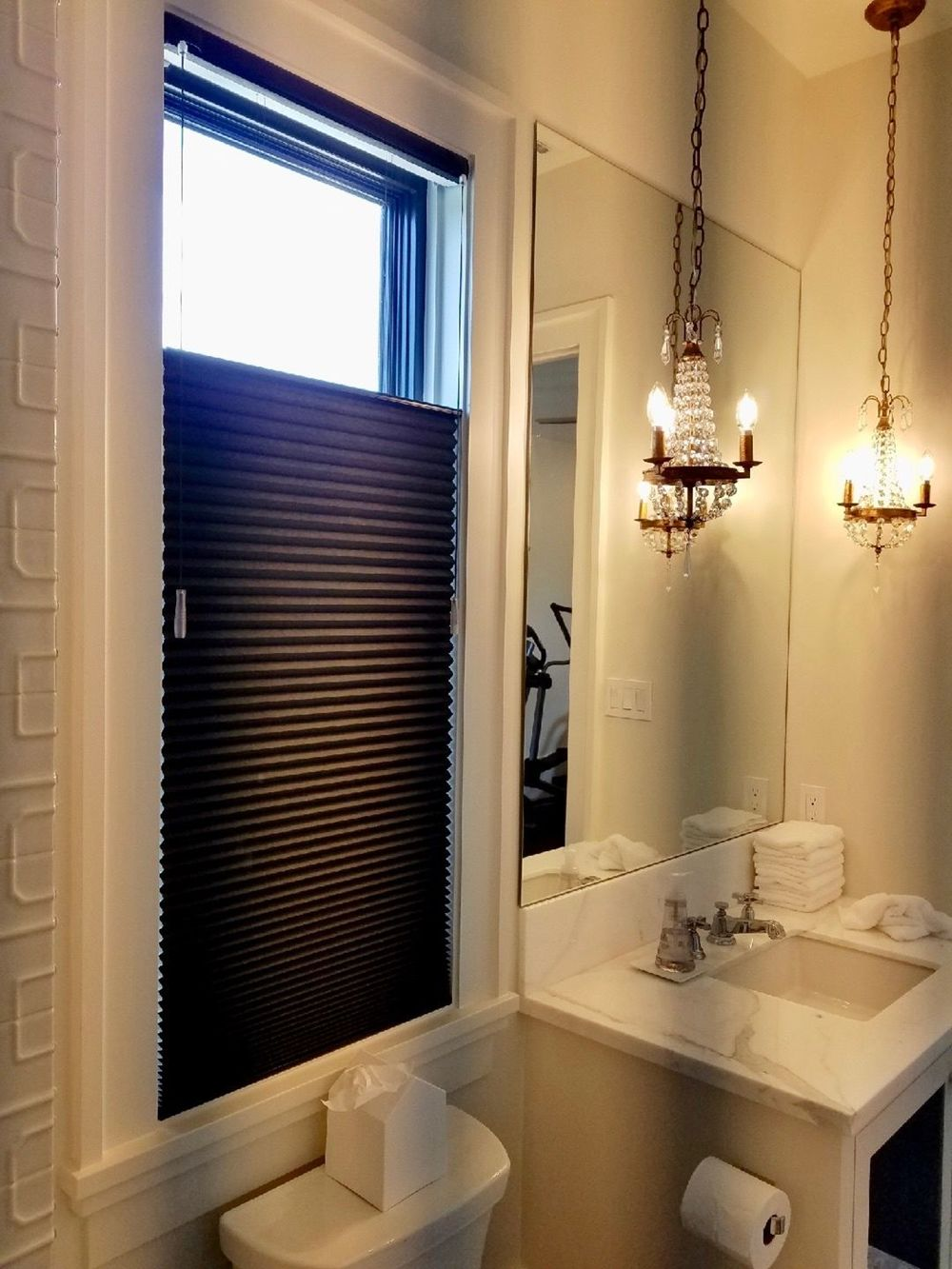 This primary bathroom offers a small single sink lighted by a gorgeous pair of chandeliers hanging from a tall ceiling.