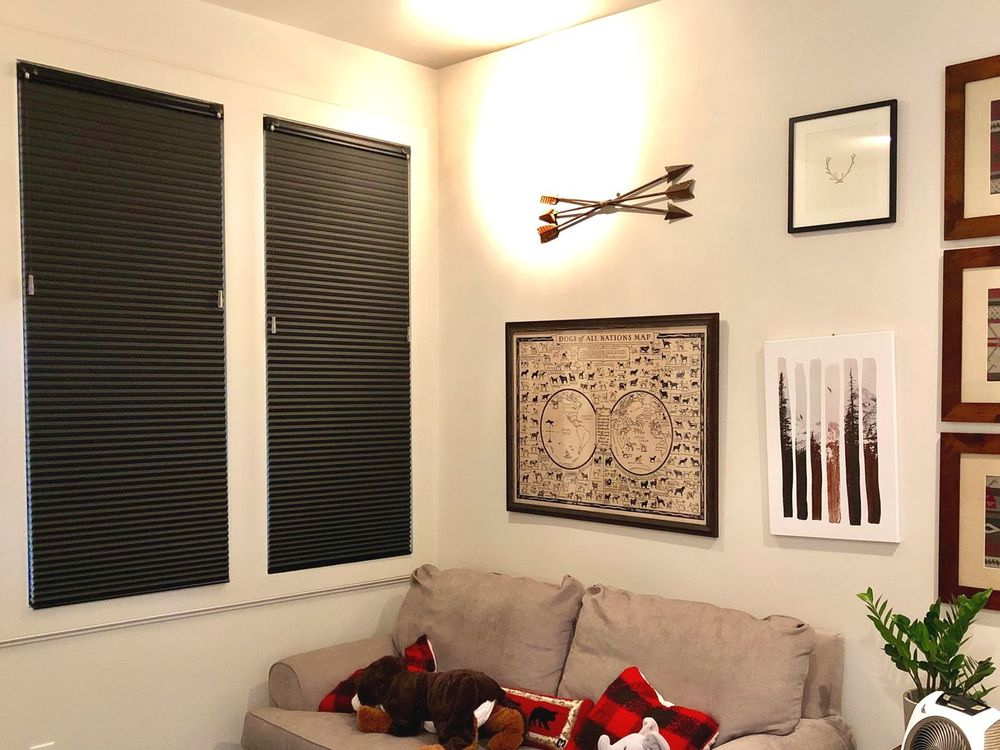This home features a set of stylish window shades on its windows. It also features attractive wall decors and warm lighting.