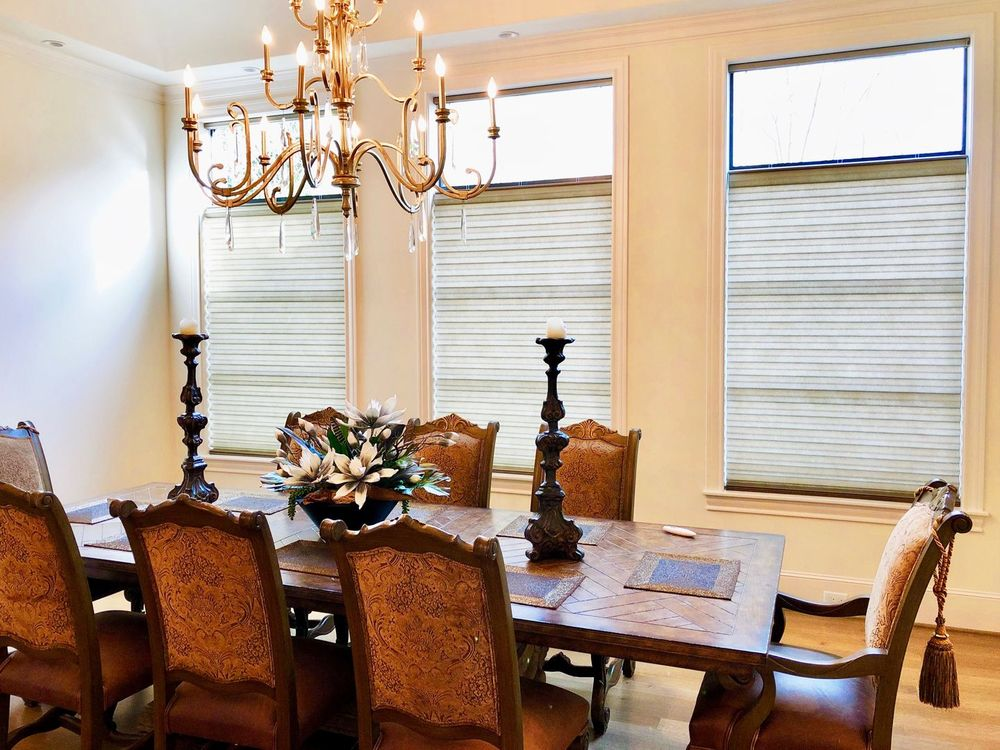 This dining room boasts an elegant dining table and chairs set that is lighted by a luxurious chandelier. The room also features windows with window shades.