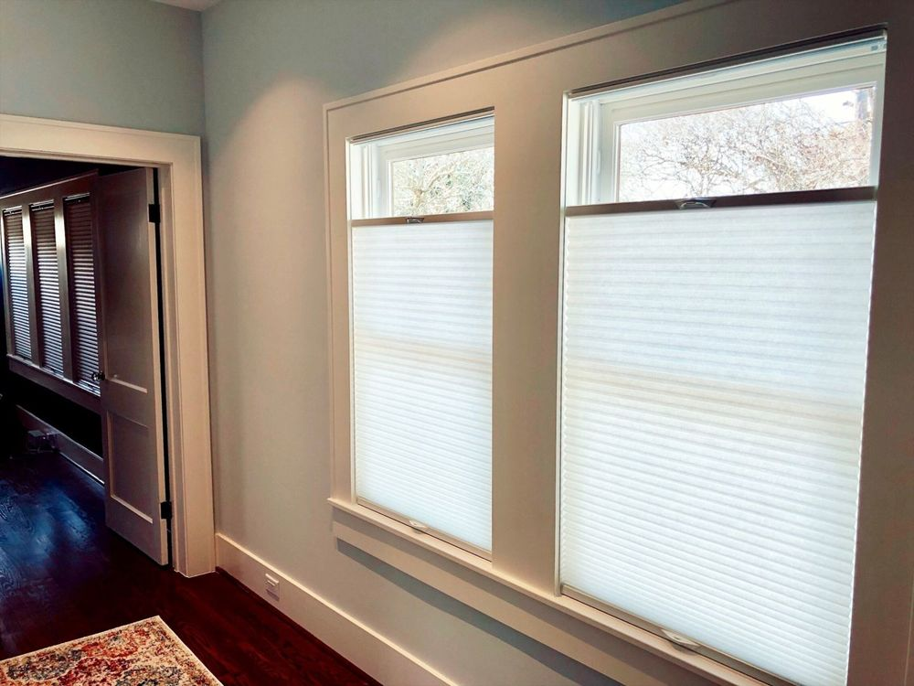 This home features reddish hardwood flooring and light gray walls, along with windows featuring window shades, as can be seen in this hallway view.