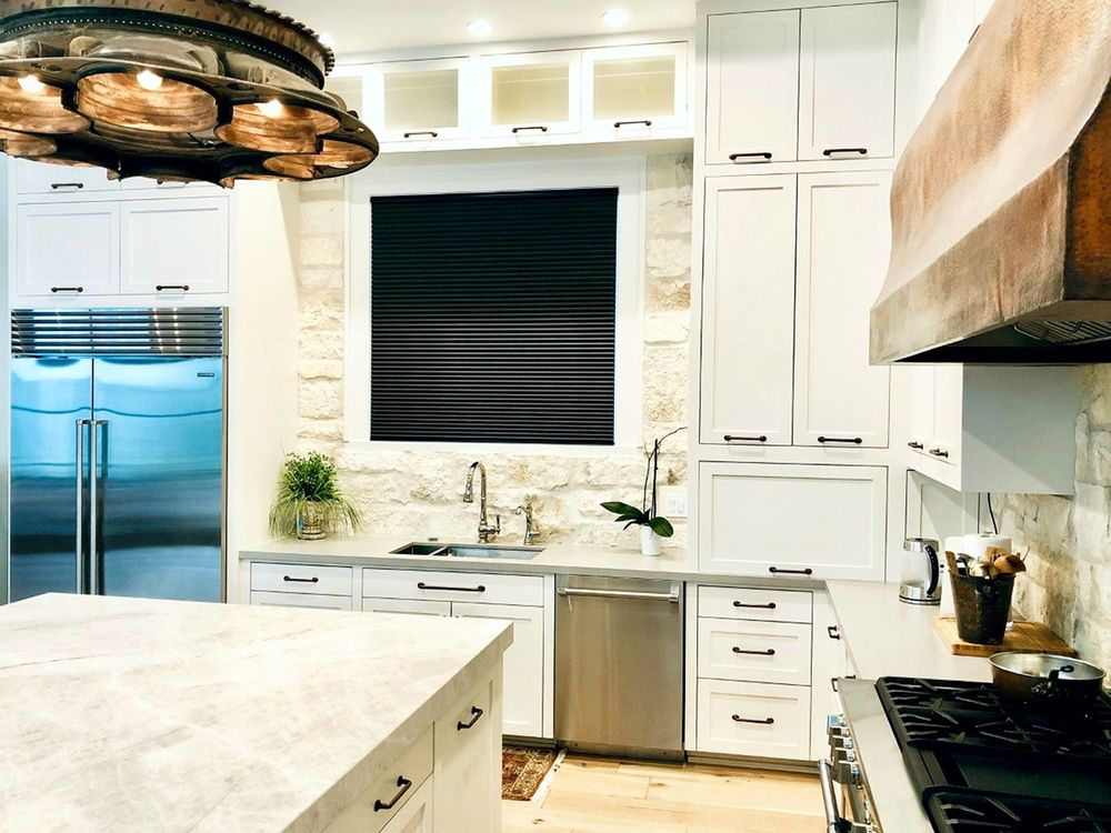 This kitchen boasts white cabinetry and an L-shaped kitchen counter, together with a large center island with a marble countertop.