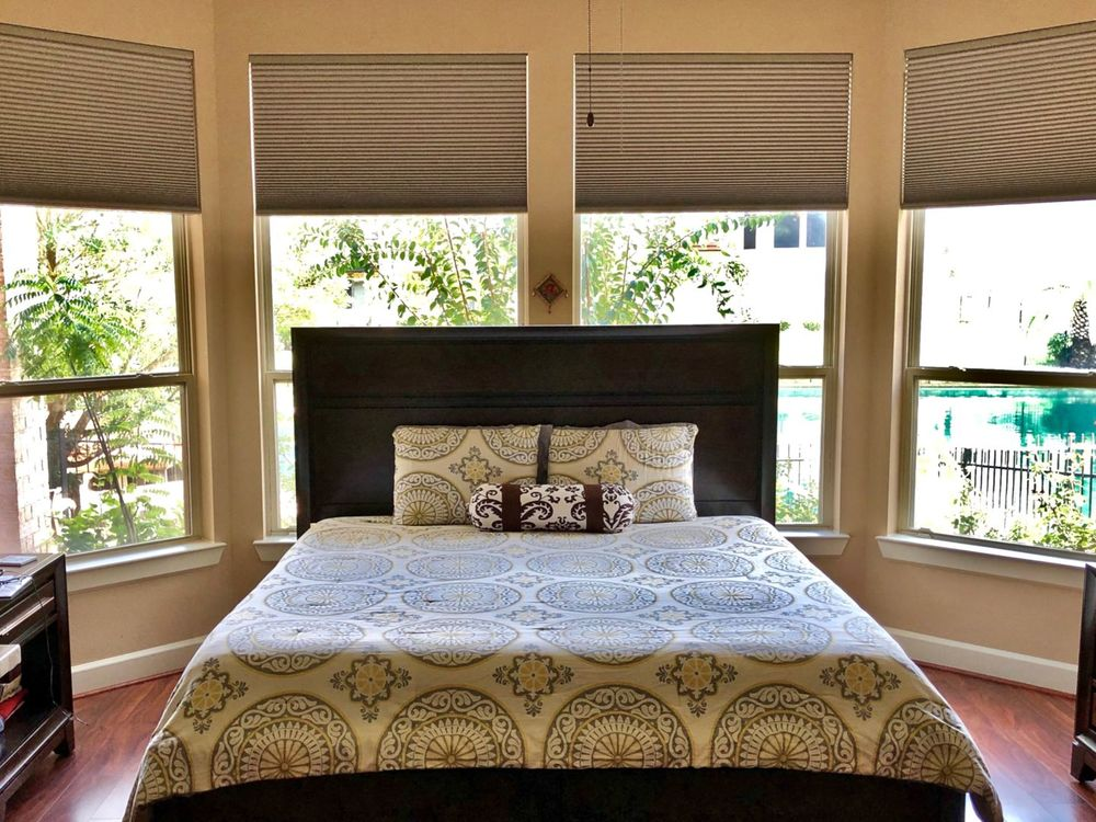 A focused look at this primary bedroom's luxurious bed setup surrounded by glass windows overlooking the outdoor amenities.