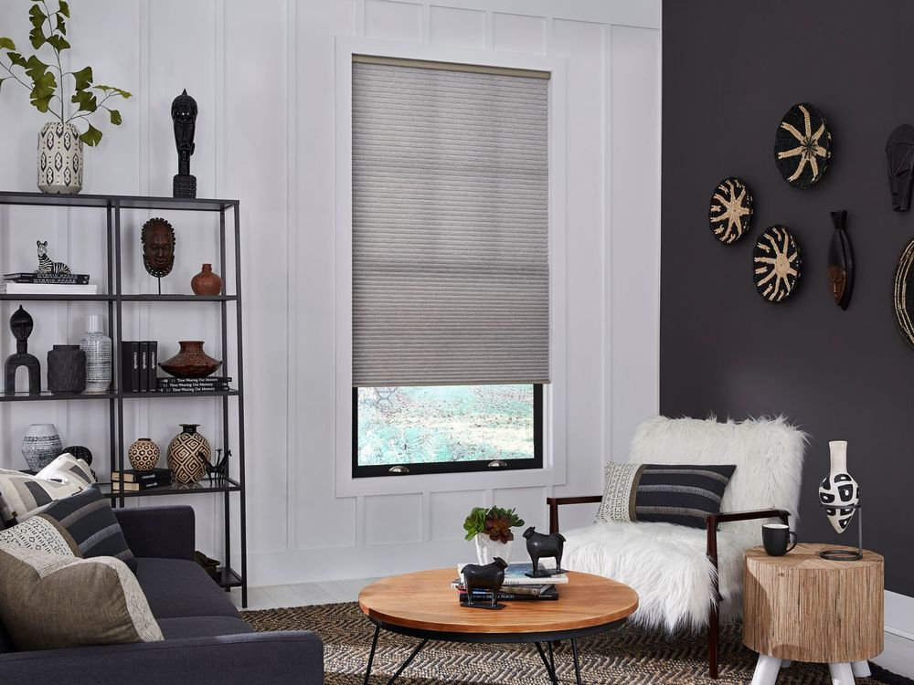A living space featuring a modern sofa set with a stylish center table, along with black and white walls and a window featuring a window shade.