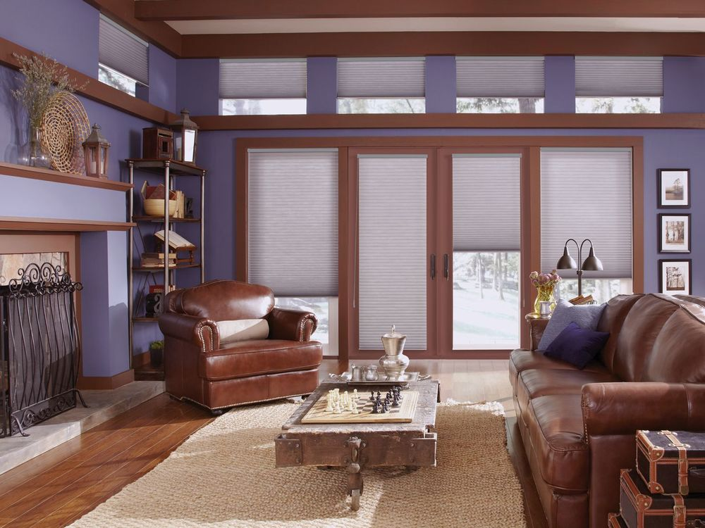 This living space boasts a set of leather seats along with a classy center table on top of a brown area rug covering the hardwood flooring. The area also has a fireplace.