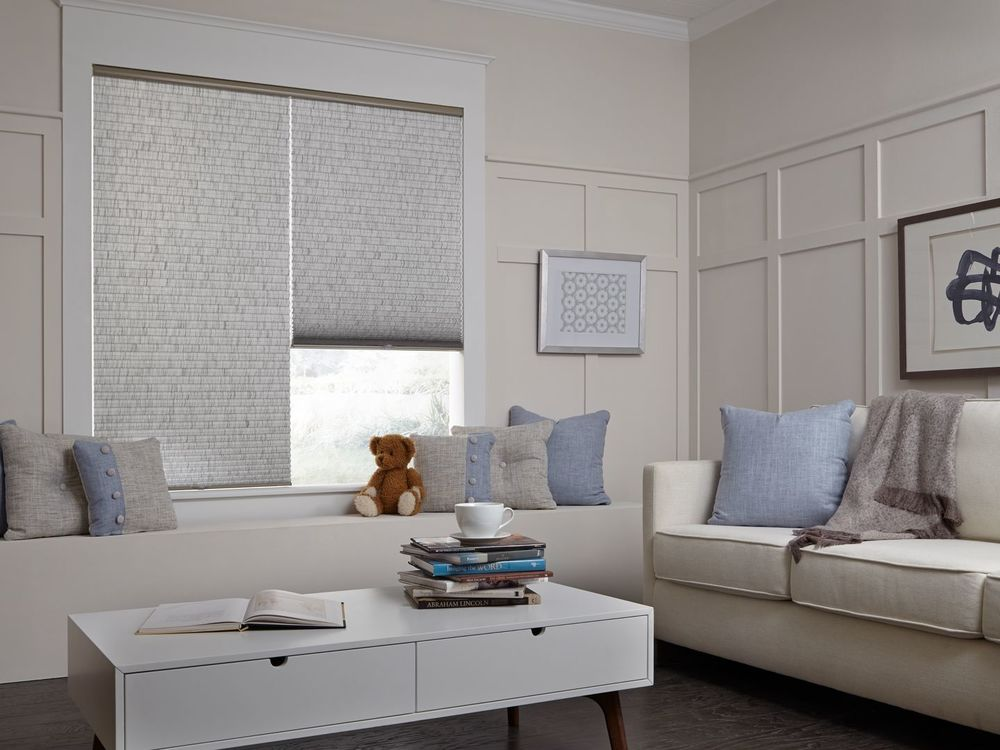 This living space offers a nice couch and a white center table set on the hardwood flooring. The glass window also features window shades.
