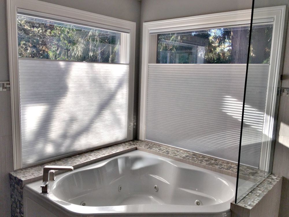 A closer look at this primary bathroom's drop-in corner deep soaking tub. The glass windows nearby feature window shades as well.
