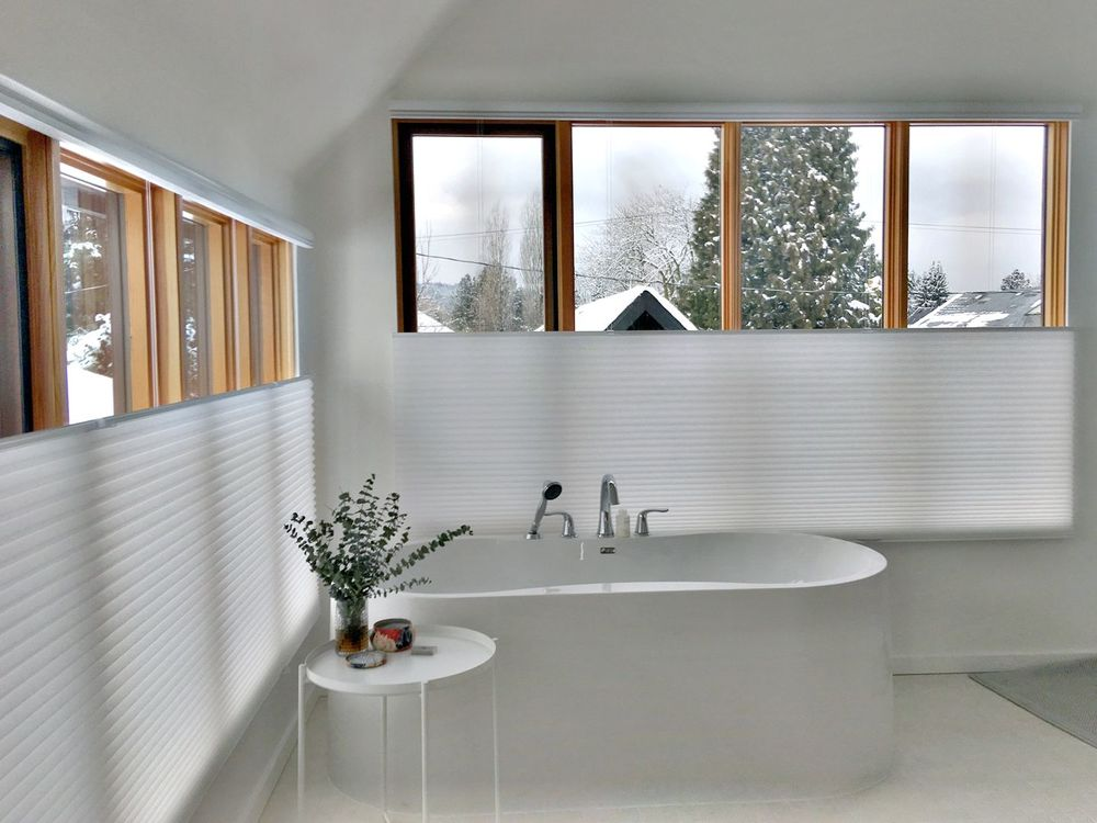 This bathroom boasts a gorgeous deep soaking tub near the glass windows covered by window shades.